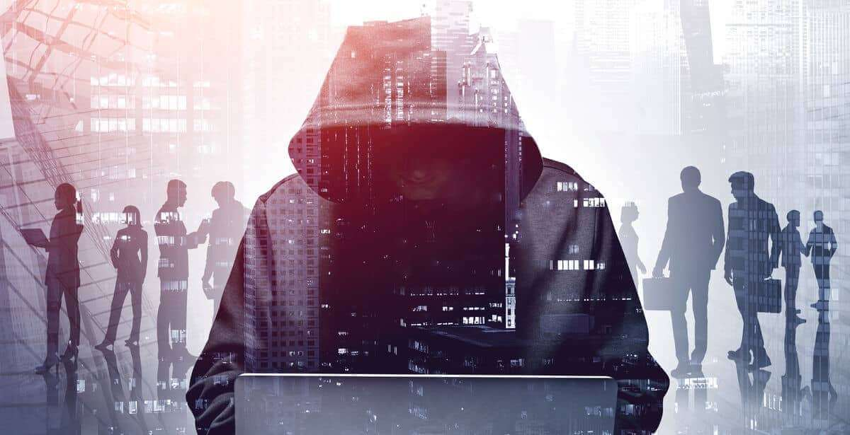 Hacker in a hoodie against a background of shadowy figures